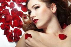 Beautiful girl on rose petals Stock Photos