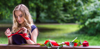 Beautiful girl with rose and red tape. In the park Stock Photos