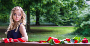 Beautiful girl with rose and red tape. In the park Stock Images