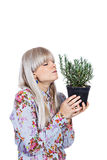 Beautiful girl with a rosemary plant. Beautiful blond girl holding fragrant potherb isolated on white background Royalty Free Stock Images