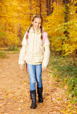 Beautiful girl with rucksack stands in forest Royalty Free Stock Photo
