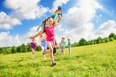 Beautiful girl run with kite together with friends stock images