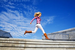 Beautiful girl running. Against blue sky Stock Images