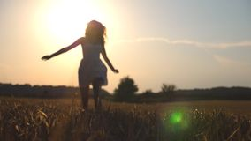 Beautiful girl is running along wheat field at sunset. Young woman jogging at the meadow and enjoing freedom. Summer