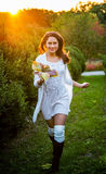 Beautiful girl running in autumn park holding leaves Royalty Free Stock Photo
