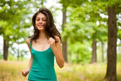 Beautiful girl running through forest. Beautiful young woman running or jogging through a forest, healthy life and sport concept Stock Photo