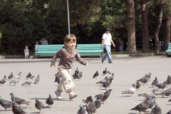 Beautiful girl running at square and pigeons. Beautiful little girl running at city square and pigeons Royalty Free Stock Images