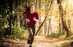 Beautiful girl running trough forest in autumn stock photos
