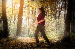 Beautiful girl running trough forest in autumn stock photography