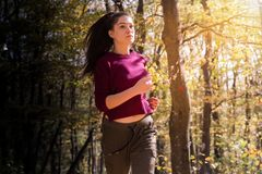 Beautiful girl running trough forest in autumn royalty free stock photo