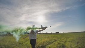 Beautiful girl runs with a toy airplane that emit colored smoke. The illusion of a working airplane. stock video footage