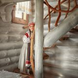 A beautiful girl in a Russian costume is standing on a wooden staircase
