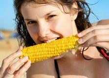 Beautiful girl's face eating corn vegetable. Beautiful girl's face. Healthy eating yellow corn vegetable royalty free stock photos