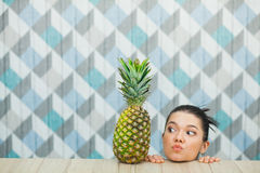 Beautiful girl`s head and fresh pineapple on wooden table. Young woman smile and blow a kiss. Healthy food concept. Copy space Royalty Free Stock Image