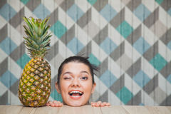 Beautiful girl`s head and fresh pineapple on wooden table. Young woman smile and wink. Healthy food concept. Copy space Stock Photo