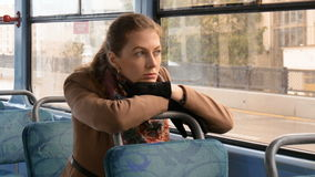 A beautiful girl with sad eyes is alone in the tram. stock footage