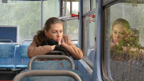 A beautiful girl with sad eyes rides in a tram. It is raining outside. She`s in a bad mood, she`s sad, bad news. Sadness and despondency Loneliness close-up stock video footage