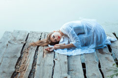Beautiful girl with sad face lying on a wooden pier. Stock Image