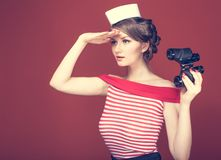 Beautiful girl sailor with a vintage binoculars and looks into the distance Stock Photography