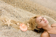 Beautiful girl on sand with cockleshells in hair Stock Images