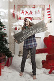 Beautiful girl in Santa Claus hat showing wooden signboard with Royalty Free Stock Photography