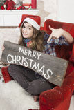 Beautiful girl in Santa Claus hat showing wooden signboard with Stock Photo