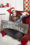 Beautiful girl in Santa Claus hat showing wooden signboard with Royalty Free Stock Image