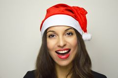 Beautiful girl with Santa Claus hat smiling at camera on white background.  Stock Image