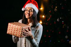 Girl in santa hat near a christmas tree with gifts Royalty Free Stock Images