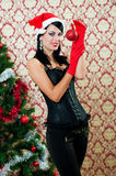 Beautiful girl in santa hat near a christmas tree Royalty Free Stock Photography