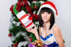 Beautiful girl in santa hat near a christmas tree Stock Image
