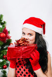 Beautiful girl in santa hat near a christmas tree Royalty Free Stock Photo