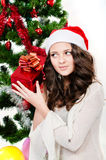 Beautiful girl in santa hat near a christmas tree Stock Images