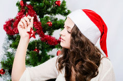 Beautiful girl in santa hat near a christmas tree Royalty Free Stock Photos