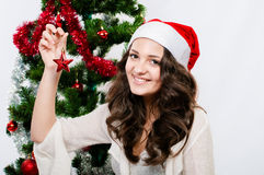 Beautiful girl in santa hat near a christmas tree Royalty Free Stock Image