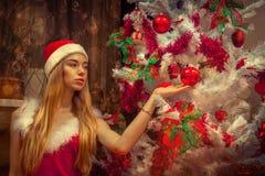 Beautiful girl in santa hat near christmas tree Royalty Free Stock Photo