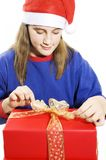 Beautiful girl in santa hat opening gift Royalty Free Stock Photos