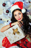 Beautiful girl in santa hat. Pretty girl holding a Christmas gift Stock Photography