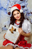 Beautiful girl in santa hat. Pretty girl holding a Christmas gift Stock Image