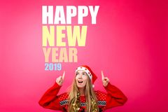 Beautiful girl in a Santa hat, with a tinsel around her neck, pointing fingers up and showing a blank space with text. Happy New. Girl in a santa hat with a royalty free stock image