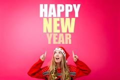 Beautiful girl in a Santa hat, with a tinsel around her neck, pointing fingers up and showing a blank space with text. Happy New. Girl in a santa hat with a stock images