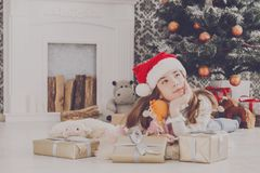 Beautiful girl in santa hat unwrapping christmas presents Stock Photos