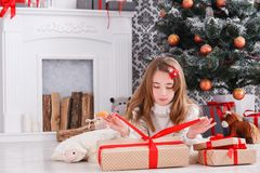 Beautiful girl in santa hat unwrapping christmas presents Royalty Free Stock Photos