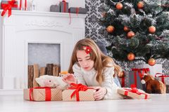 Beautiful girl in santa hat unwrapping christmas presents Royalty Free Stock Photography