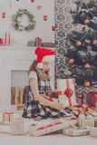 Beautiful girl in santa hat unwrapping christmas presents. Beautiful happy girl in santa hat unwrap christmas present box on holiday morning in beautiful room Stock Images