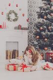 Beautiful girl in santa hat unwrapping christmas presents. Beautiful happy girl in santa hat unwrap christmas present box on holiday morning in beautiful room Stock Photo
