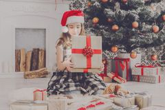 Beautiful girl in santa hat unwrapping christmas presents. Beautiful happy girl in santa hat unwrap christmas present box on holiday morning in beautiful room Royalty Free Stock Image