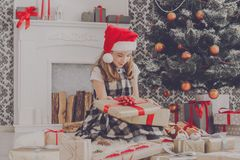 Beautiful girl in santa hat unwrapping christmas presents Stock Photo