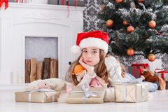 Beautiful girl in santa hat unwrapping christmas presents Royalty Free Stock Image