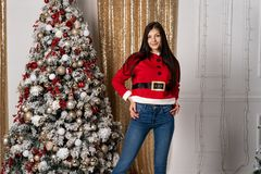 Beautiful girl in santa sweater after decorating the Christmas tree posing, looking at the camera stock image